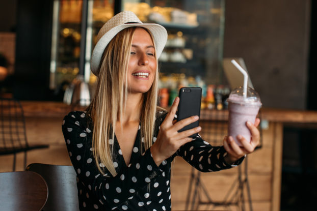 woman taking picture of milkshake with phone