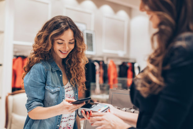 woman paying in clothing store with phone