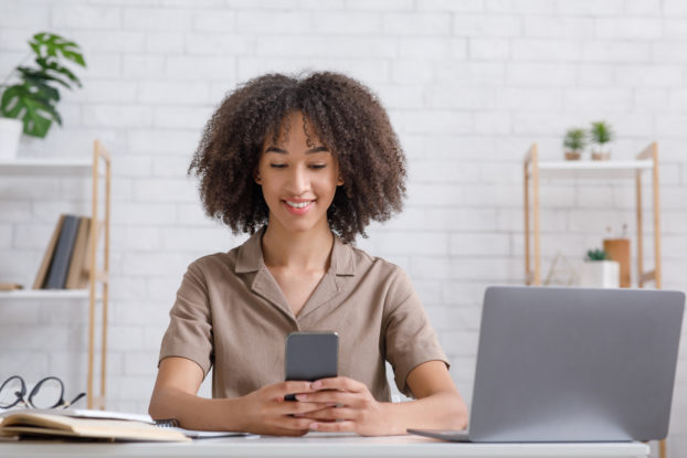 A smiling woman looks at her smartphone. An open laptop sits at her elbow.