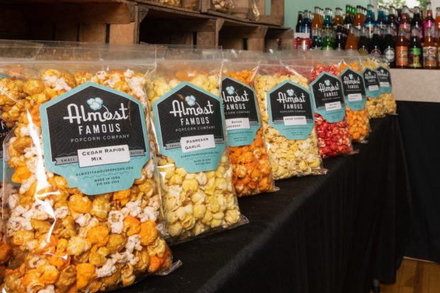 Almost Famous Popcorn bags of popcorn displayed on store shelves.