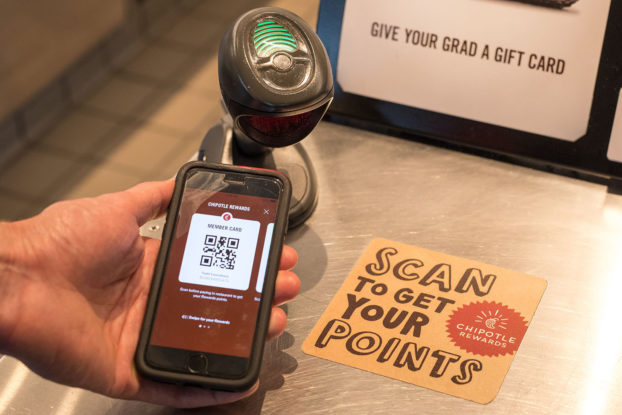 Person using barcode on phone to scan for Chipotle Rewards program.