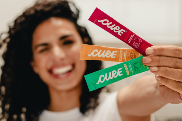 woman smiling holding up cure hydration drink packets