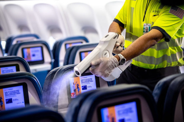 worker on delta plane using sanitizer machine