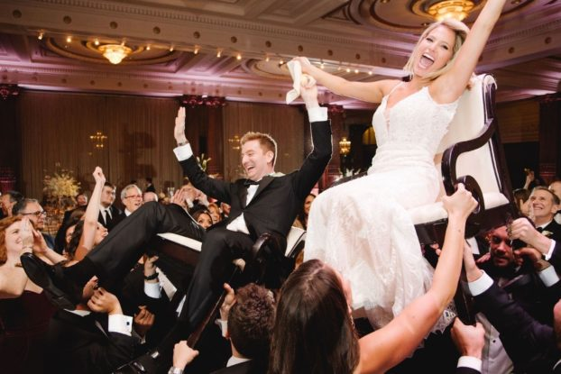 Scene from a wedding with bride and groom lifted in chairs.