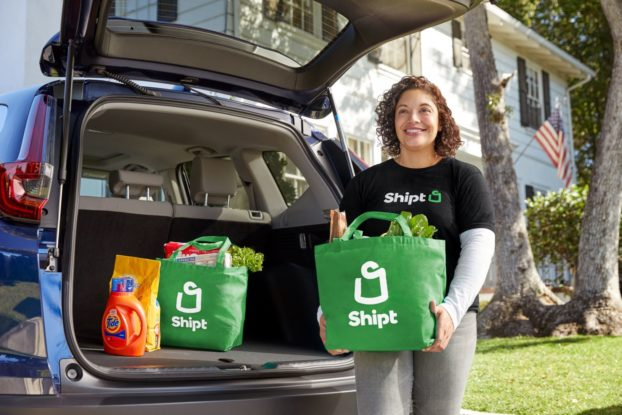 A Shipt driver unloads groceries in green Shipt bags from the trunk of a blue car.