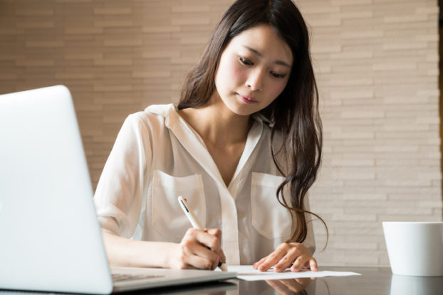 woman filling out paperwork next to computer