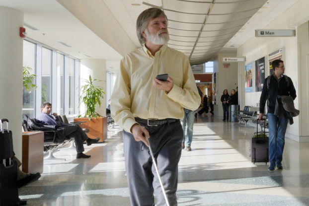 man with cane using indoor explorer app