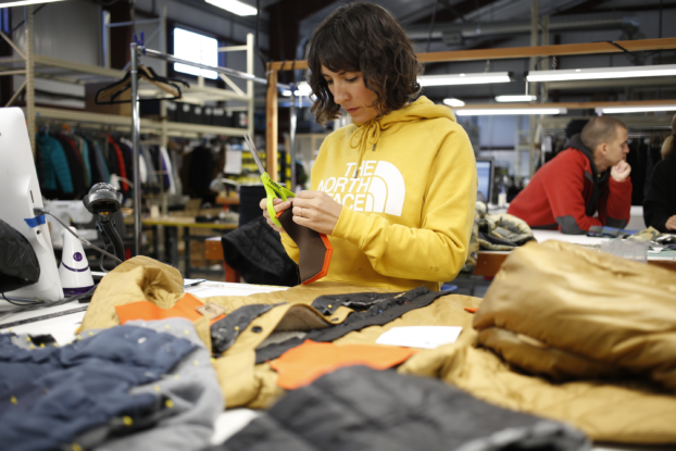 the north face employee working on clothing for renewed initiative