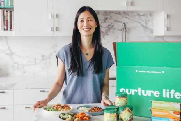 Jennifer Chow, co-founder of Nurture Life, posing in a kitchen with the unboxed meals.