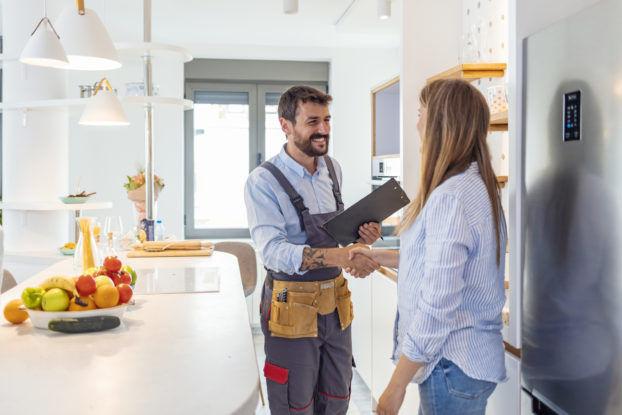 Handyman shakes client's hand after completing a job.