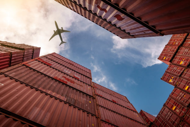 Plane flies above shipping containers at industrial port