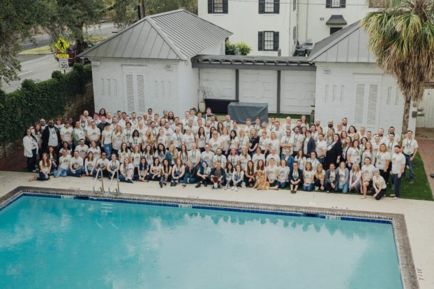 Business staff take a group photo near a building and pool