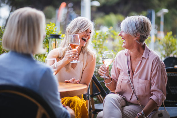 Women laugh over wine at an outdoor restaurant