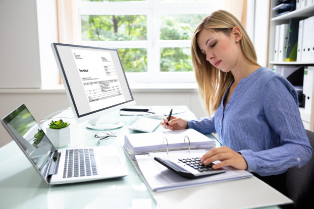 A woman consults a calculator while writing something in a binder full of papers. Both a laptop and a computer monitor sit on the desk near her, with the monitor displaying an invoice..