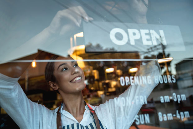 woman hanging an open sign on door of business