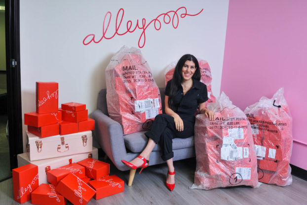 Alleyoop CEO and founder, Leila Keshani, sitting on a couch surrounded by bags of her products.