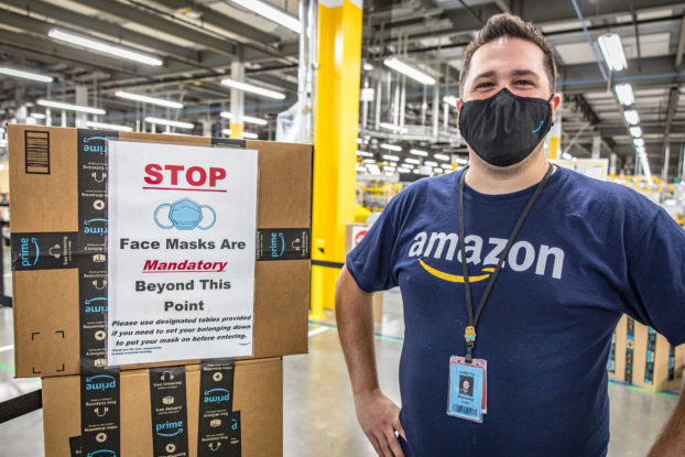 amazon employee wearing mask next to covid-19 safety sign