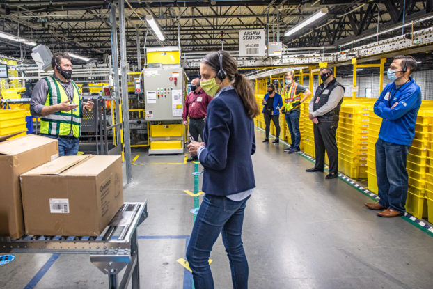 amazon employees working socially distanced in fulfillment center