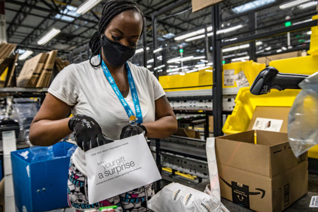 amazon employee in mask and gloves packing items