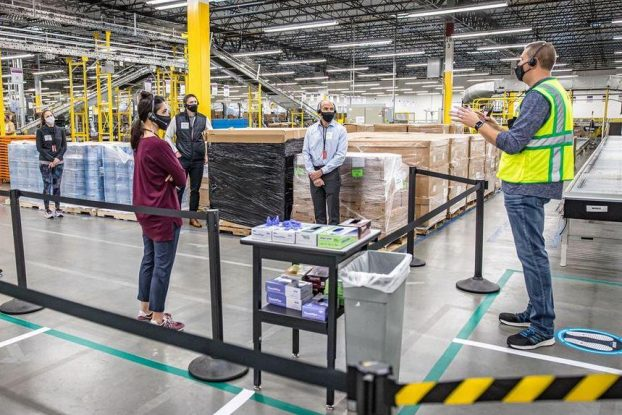 Amazon employee speaking to people inside the warehouse.