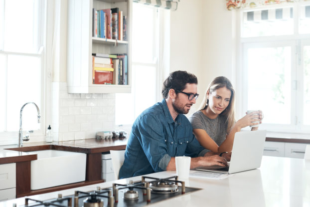 two people in kitchen working on laptop