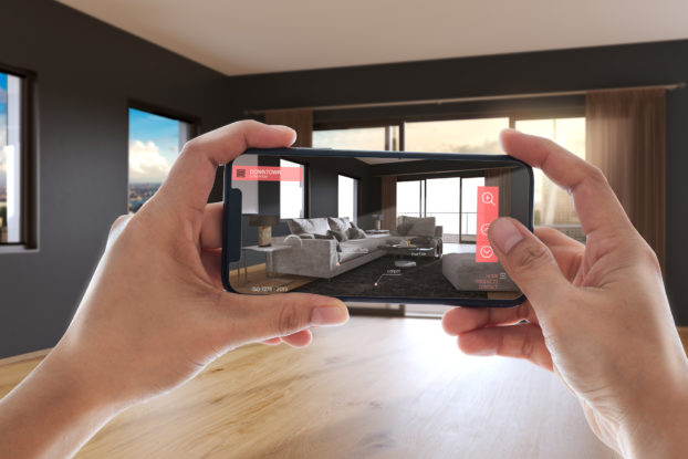 Person using an augmented reality app on their phone to picture furniture in their space before buying.