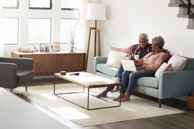 elderly couple sitting on couch with laptop
