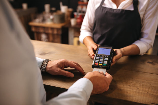 man paying in cafe with credit card