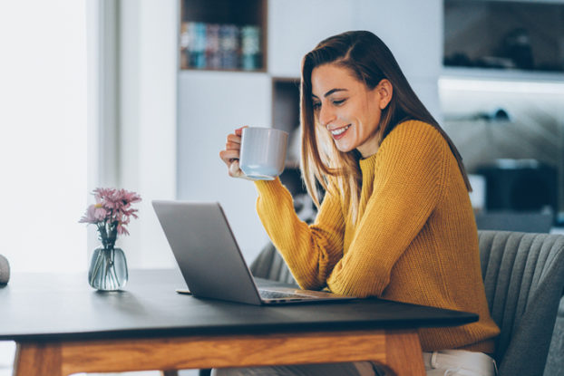 woman at table with laptop having coffee