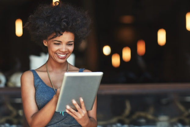 woman looking at tablet smiling