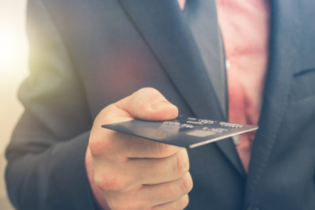 man in suit holding out a credit card