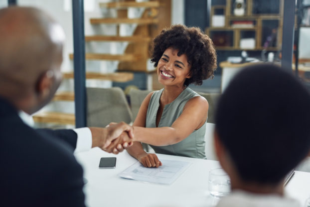 man and woman shaking hands in a job interview