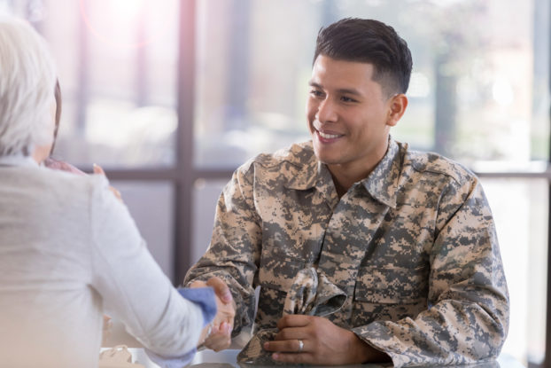 soldier in uniform shaking hands with woman