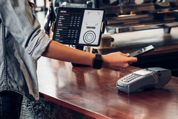 Woman paying at cafe with contactless mobile payment.