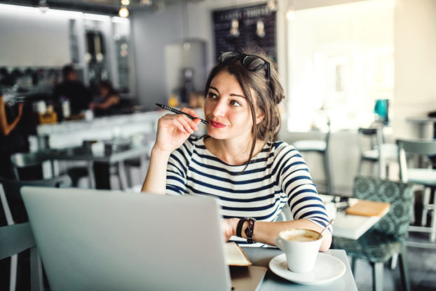 woman sitting at laptop with coffee