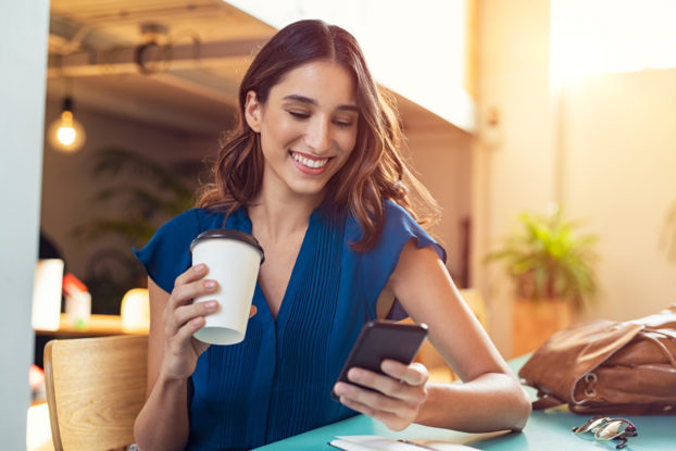 woman holding coffee looking at smartphone