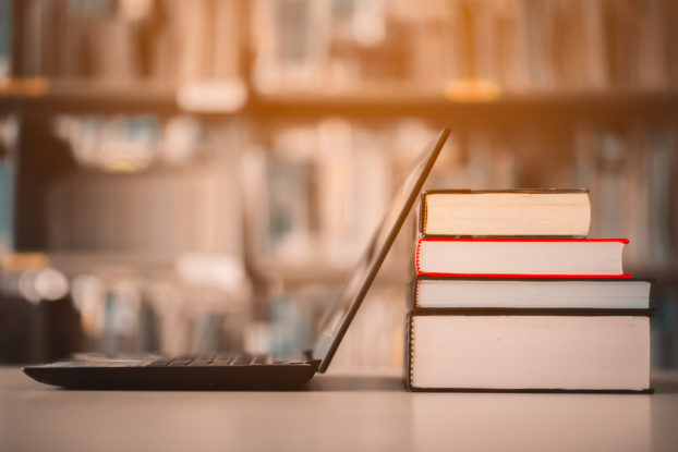 laptop on table with books