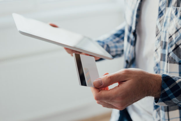 person holding tablet and credit card