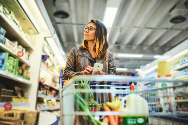 woman grocery shopping with phone in her hand