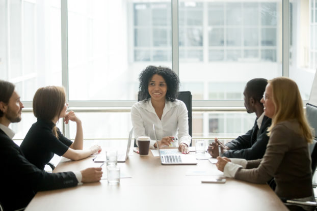 A diverse group -- three woman and two men of various races -- sits around a conference room table. At the head of the table is a smiling Black woman; behind her is a floor-to-ceiling window..