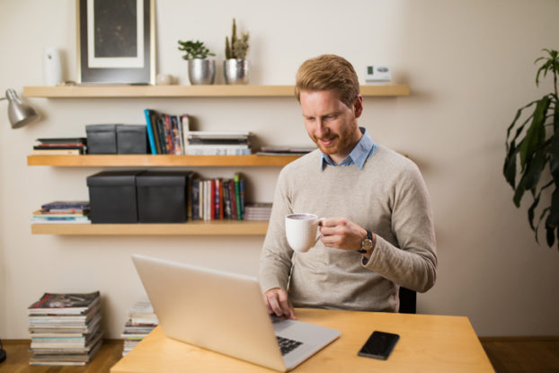 Man with coffee at laptop