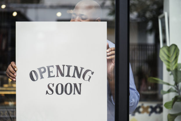 man hanging 'opening soon' sign in window