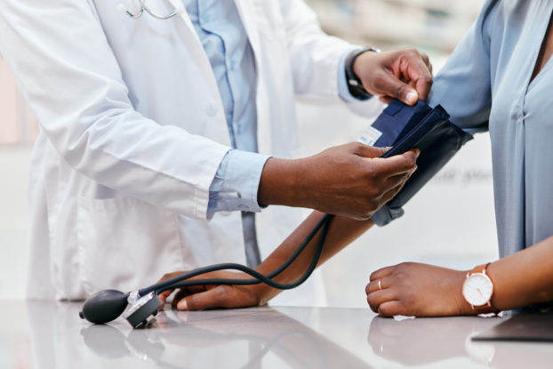 A shoulders-down shot of a doctor in a white lab coat administering a blood pressure test.