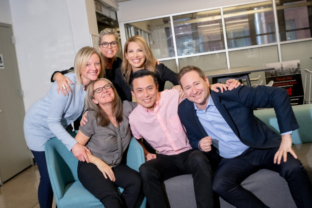 Men and women smile in a workplace lounge