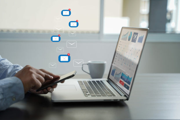 man's hands on phone and laptop with email icons