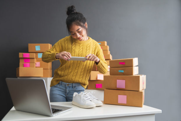 A woman in a bright yellow sweater takes a picture of a pair of white sneakers with her smartphone. She is surrounded by labelled cardboard boxes and an open laptop.