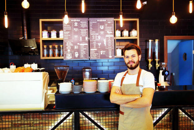 A man wearing an apron stands in front of a coffee shop counter, behind which is mounted a menu.