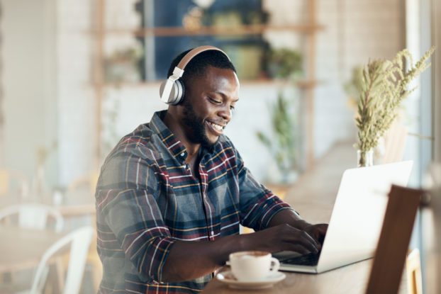 man wearing headset working on laptop