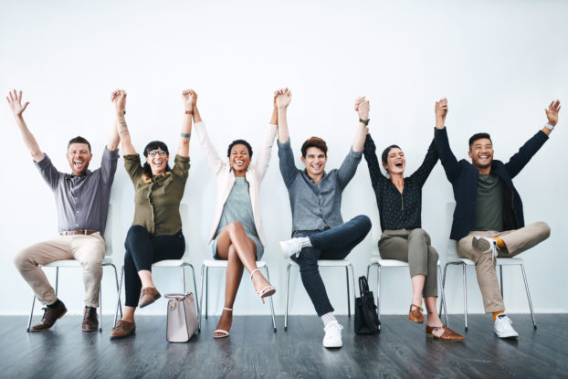 team of employees holding hands in the air