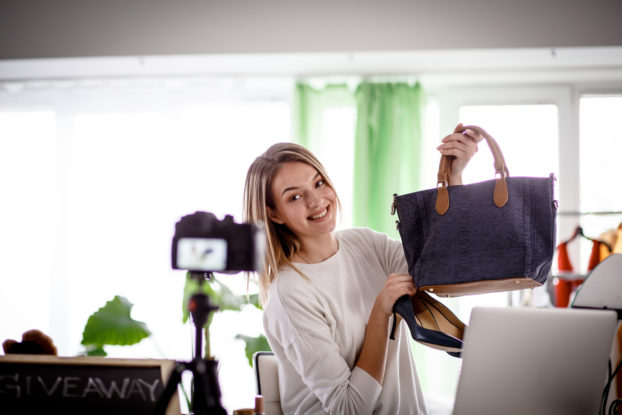 female influencer holding pocketbook in front of camera